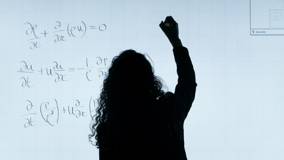 person doing math on whiteboard